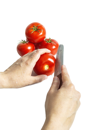 Female hands with knife, cutting fresh red tomatoes. Selective focus.