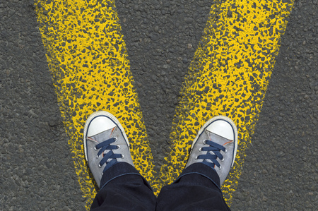 Sneakers stand on asphalt pavement with the yellow road marking lines Stock Photo