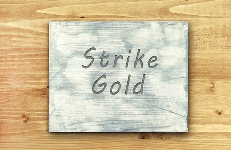 phrase: Vintage hipster motivational phrase note, Strike Gold sign Stock Photo