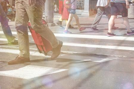 Pedestrians crossing a street with bokeh lights. Urban rush hour Stock Photo