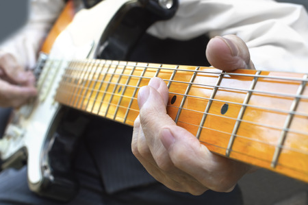 Elderly musician playing electric guitar. Selective focus.