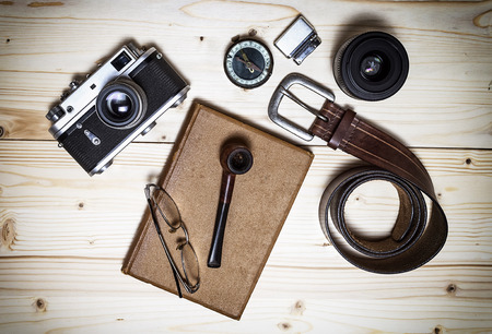 Stil: Still life with retro object. Book with compact old camera, compass, cigarette lighter, belt, glasses, pipe, dslr lens on wood table.
