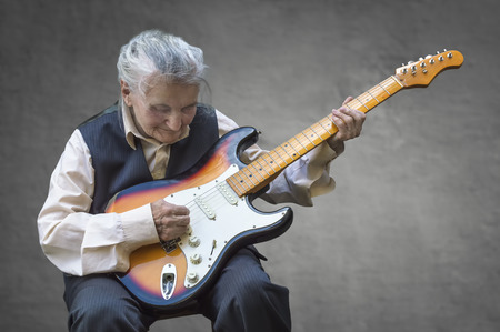 Elderly woman playing guitar. Selective focus.