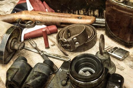 Still life with retro object. Bell, rifle, shot, binoculars, usa flag, belt, canteen, flask, lighter, knife, fork, camera. Selective focus.