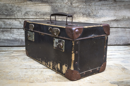 Vintage suitcase isolated on wooden table. Selective focus.