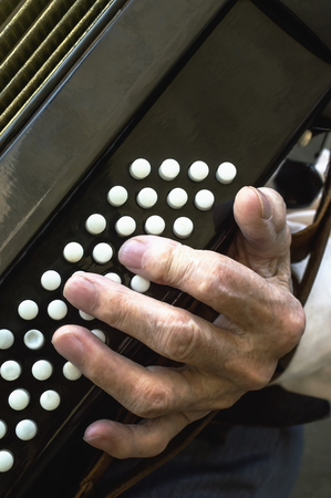 Details of a hand on an old accordion while playing. Selective focus.