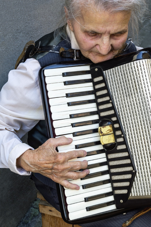 Elderly woman playing old accordion.
