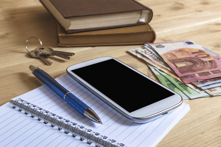 Still life photo of smartphone, notebook, book, pencil, money and keys on wooden table. Selective focus.