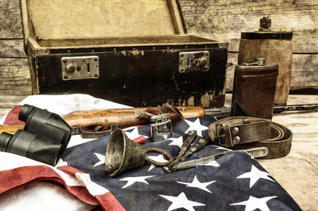 Still life with retro object. Suitcase, bell, rifle, shot, binoculars, usa flag, belt, canteen, flask, lighter, knife, fork. Selective focus. Stock Photo