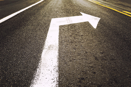 Turn right white arrow sign on the road