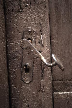 Close up image of old wooden door with metal knob.