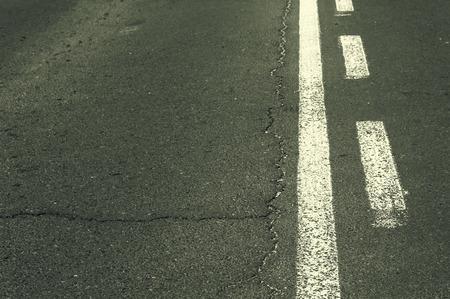Double white grunge line on asphalt road.