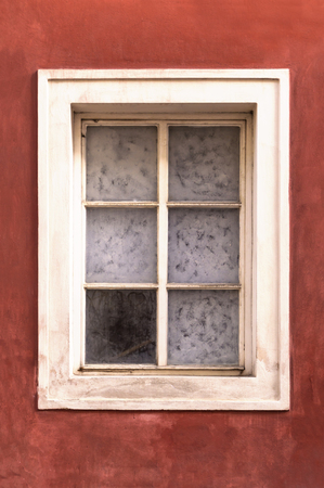 Old window on an old red stucco wall
