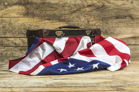 USA flag with old style voyage suitcase. Selective focus.