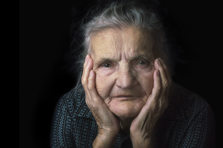 evoking: Portrait of a sad, nostalgic elderly woman. Evoking the past and worrying about the future. Selective focus. Stock Photo