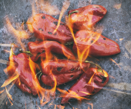 double oven: Roasted red peppers in flame on the barbecue, double exposure. Selective focus. Stock Photo