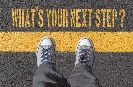 Qual è il tuo prossimo passo ?, stampa con scarpe da ginnastica su strada asfaltata, vista dall'alto.