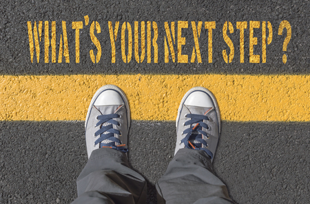 What`s your next step?, print with sneakers on asphalt road, top view. Фото со стока