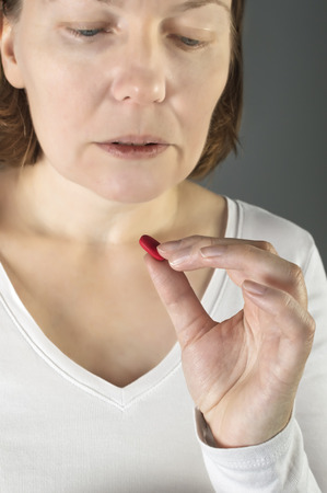 Close up of woman taking in pill. Medicine, health care concept.
