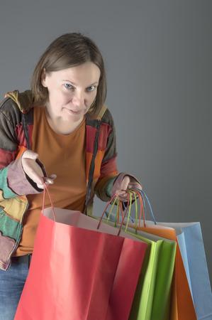 Shopping woman holding shopping bags. Female model isolated studio background.