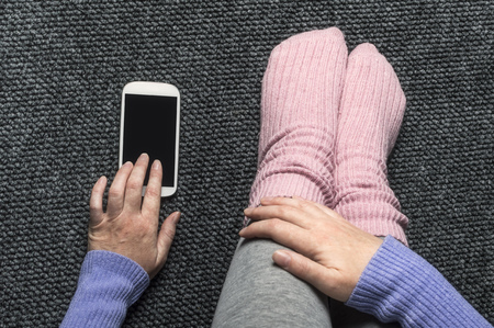 Woman sitting on the floor with smartphone, top view point. Stock Photo