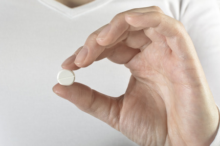 Pills in woman hand, close up.