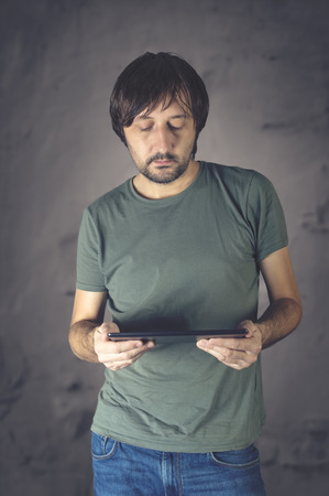 Serious young male using digital tablet against dark background. Business concept. Stock Photo