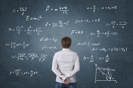 Business person standing in front of mathematical formula. Science concept. Stock Photo