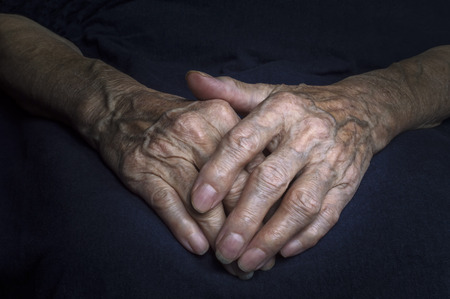 Hands of an old woman with wrinkled and wrinkles on dark background. Stock Photo