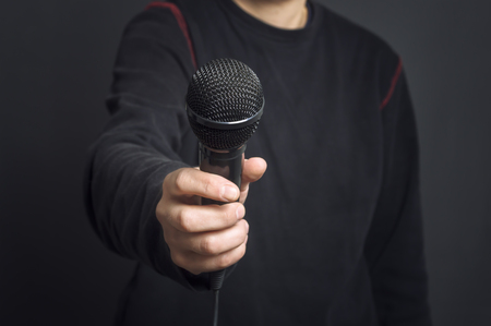 Journalist making speech with microphone and hand gesturing concept for interview. Selective focus. Stock Photo