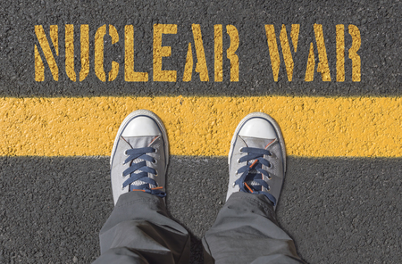 hydrogen bomb: NUCLEAR WAR print with sneakers on asphalt road, top view.