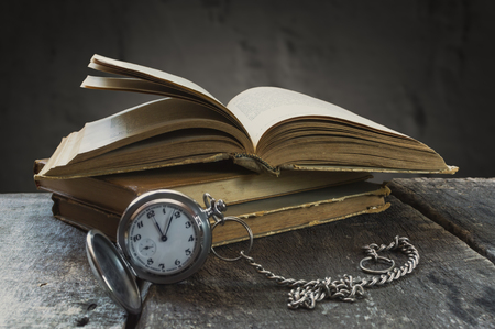 Still life with old pocket watch and books. Selective focus. Stock Photo