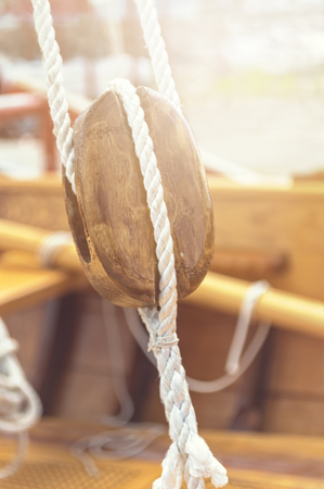 Old wooden sailboat pulleys and ropes detail. Selective focus Stock Photo