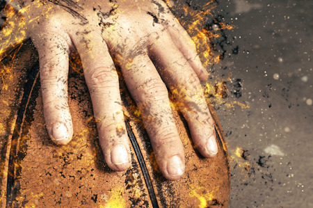 fragment of a basketball ball in a hand, fire illustration.