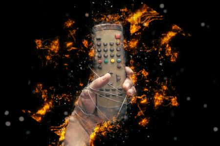 대중 매체의 자유, 대중 매체의 억압 또는 표현의 자유에 대한 아이디어를 묘사 한 유선 리모컨으로 된 손.