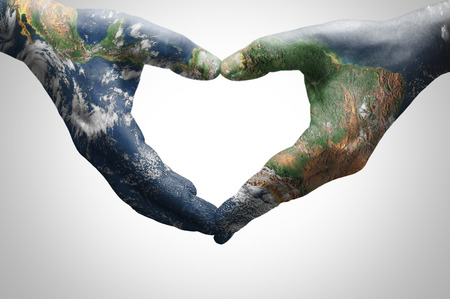 The hands of a young woman forming a heart patterned with a world map (furnished by NASA)