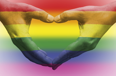 Hands painted as the rainbow flag forming a heart, symbolizing gay love.