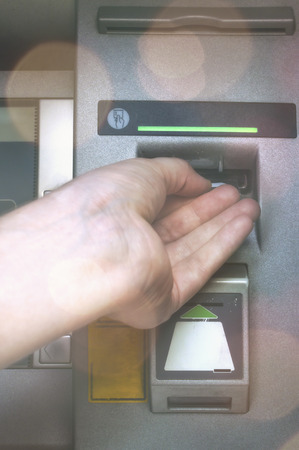 Man using teller machine - Inserts a card. Debit card transaction Stock Photo
