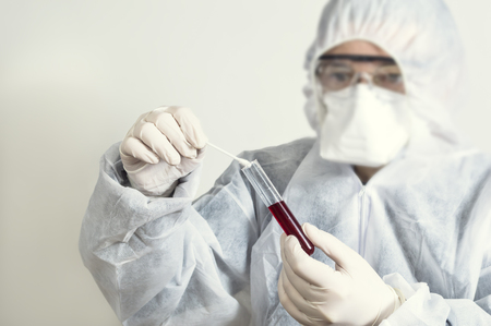 Scientist wearing protective suit and examining a test tube.
