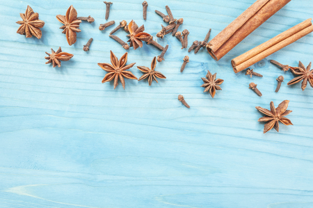 Star anise, cinnamon sticks and cloves on a nintage background. Selective focus. Stock Photo