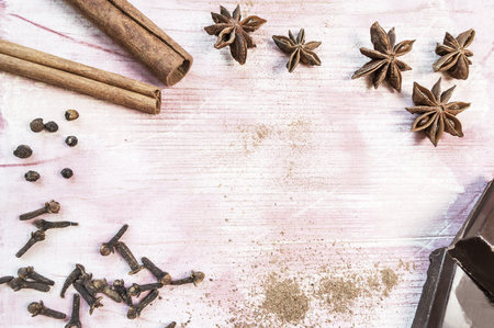 Star anise, chocolate, cinnamon and cloves on wooden table. Selective focus. Top view or flat lay