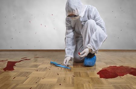 Investigación de la escena del crimen, tomando una muestra de ADN de una mancha de sangre con un algodón en la escena del crimen.