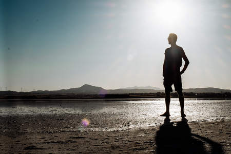 Single man walking on dry salt lake in Limassol, Cyprus. Alone and walking in desert conditions.