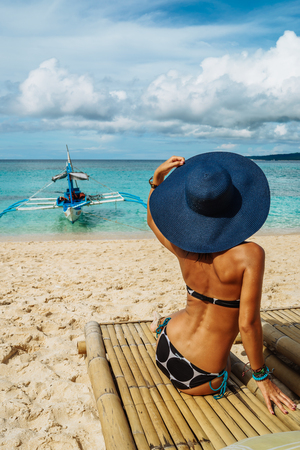 Woman with blue hat relaxing on the bamboo chair on a beautiful white beach. Philippines. Boat on the background