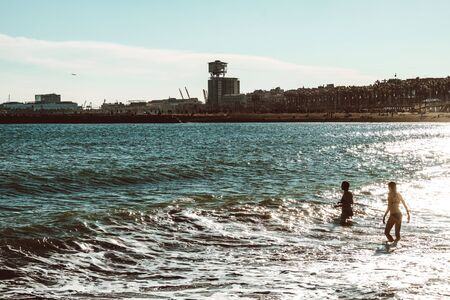 Barcelona, Spain. February, 2019. View of La Barceloneta beach on a sunny and hot winter day Редакционное