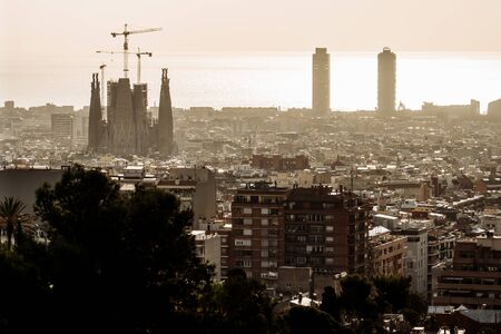 BARCELONA, SPAIN - February 2019: View of Barcelona on a cloudy day with a layer of air pollution. Photo taken from Park Guell: cityscape, skyline