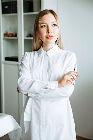 portrait of smiling cosmetologist in white coat standing at empty massage table in salon