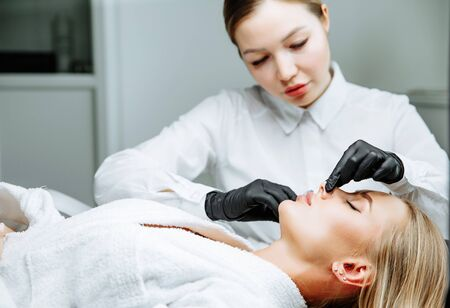 The doctor cosmetologist makes prick in the nose to correct the hump of a beautiful woman in a beauty salon. Cosmetology skin care. Stockfoto