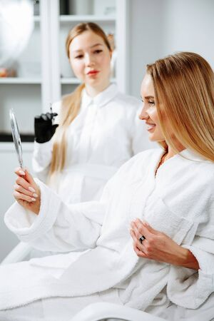 Young female client received cosmetic face treatments in clinic of aesthetic medicine, looking in mirror at results Stockfoto
