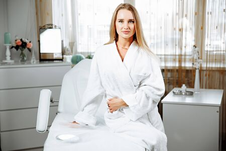 Portrait of beautiful woman in white bathrobe sitting on daybed. She is looking at camera and smiling